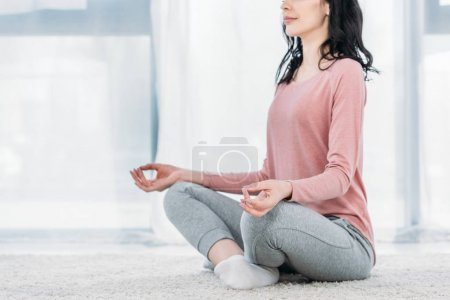 Photo for Cropped view of woman in Lotus Pose practicing meditation at home in Living Room - Royalty Free Image