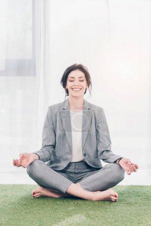 hermosa mujer de negocios sonriente en traje meditando mientras está sentado en la alfombra de hierba en Lotus Pose