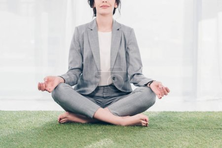 Photo for Cropped view of businesswoman in suit meditating while sitting on grass mat in Lotus Pose - Royalty Free Image
