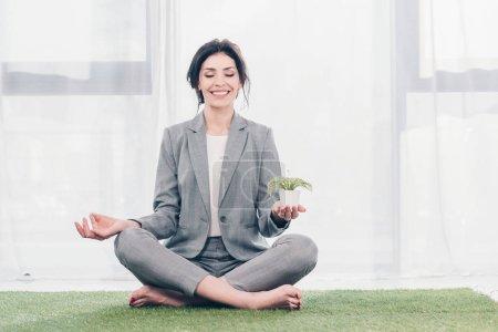 hermosa mujer de negocios sonriente sentada en la alfombra de hierba en Lotus Pose, meditando y sosteniendo maceta