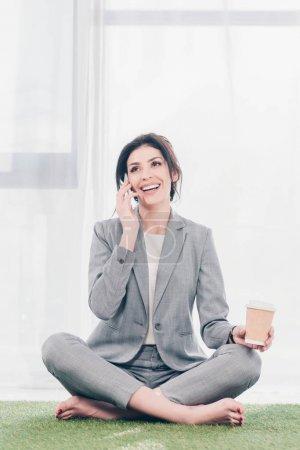 Photo pour Belle femme d'affaires souriante en costume assis sur tapis d'herbe, tenant du café pour aller et parler sur smartphone - image libre de droit