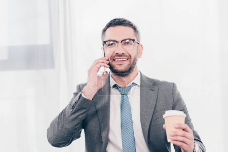 Photo for Handsome smiling businessman in glasses and suit with coffee to go talking on smartphone - Royalty Free Image