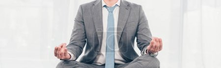 Photo pour Panoramic shot of businessman in suit meditating in Lotus Pose - image libre de droit
