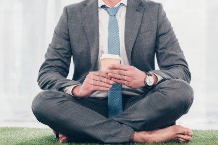 Photo pour Vue recadrée de l'homme d'affaires en costume avec café pour aller assis sur tapis d'herbe - image libre de droit