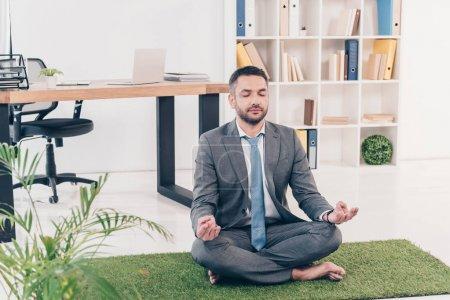 Photo pour Homme d'affaires assis sur tapis d'herbe dans Lotus Pose et méditer dans le bureau - image libre de droit