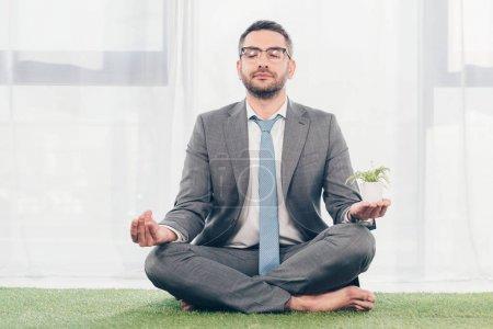 Photo pour Homme d'affaires dans des glaces sur le tapis d'herbe méditant tout en s'asseyant dans la pose de Lotus - image libre de droit