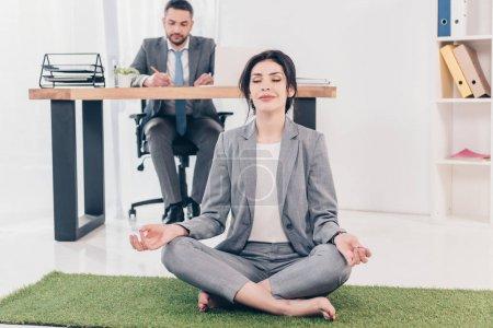 Photo pour Femme d'affaires méditant dans la pose de Lotus sur le tapis d'herbe tandis que l'homme d'affaires s'asseyant à la table et écrivant au bureau dans le bureau - image libre de droit