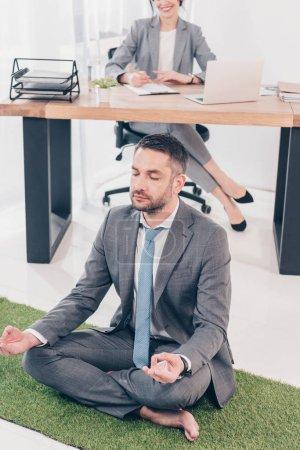 Photo pour Homme d'affaires méditant dans la pose de Lotus sur le tapis d'herbe tandis que la femme d'affaires s'asseyant à la table dans le bureau - image libre de droit