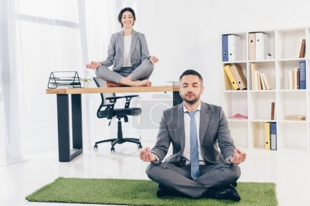 Photo for Businessman meditating on grass mat while businesswoman sitting on table in Lotus Pose in office - Royalty Free Image