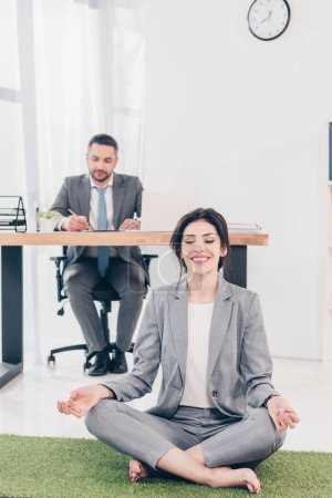 Photo pour Smiling businesswoman meditating in Lotus Pose on grass mat while businessman sitting at table and writing at desk in office - image libre de droit