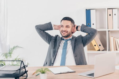 handsome smiling businessman in suit with Hands Behind Back sitting at desk in office