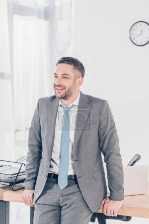 handsome businessman in suit smiling and looking away in office