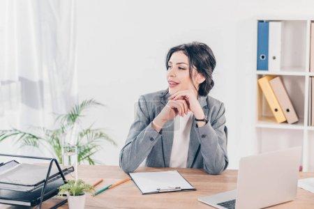 Photo pour Belle femme d'affaires en costume assis à table avec presse-papiers et ordinateur portable au bureau - image libre de droit