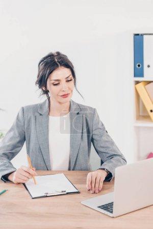 Photo pour Belle femme d'affaires en costume assis à table avec presse-papiers et en utilisant un ordinateur portable au bureau - image libre de droit