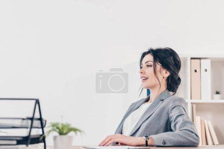 Foto de Hermosa mujer de negocios en traje sentado en la oficina con espacio para copias - Imagen libre de derechos