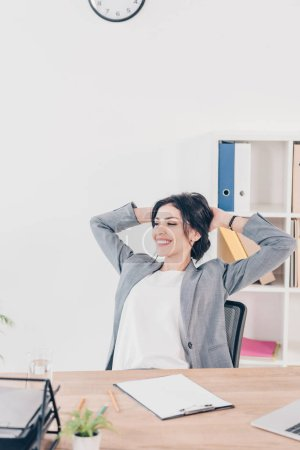 beautiful smiling businesswoman in suit with hands on head sitting at table in office