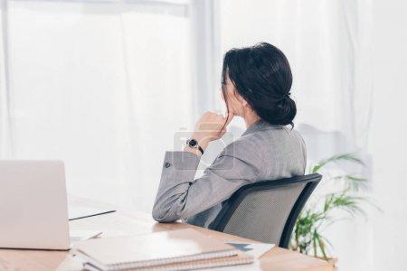 Photo pour Vue arrière de la femme d'affaires en costume assis à la table dans le bureau - image libre de droit