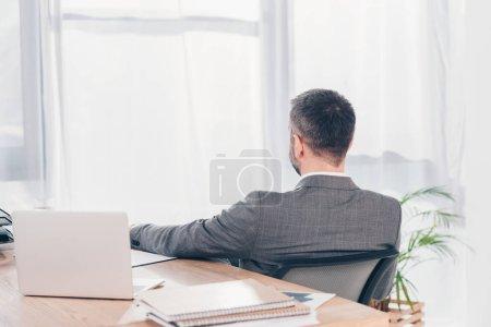 Foto de Vista trasera del hombre de negocios sentado a la mesa con la computadora portátil en la oficina - Imagen libre de derechos