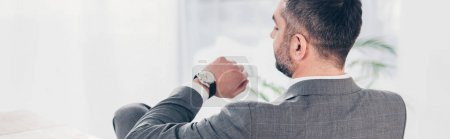 panoramic shot of businessman looking at watch and checking time
