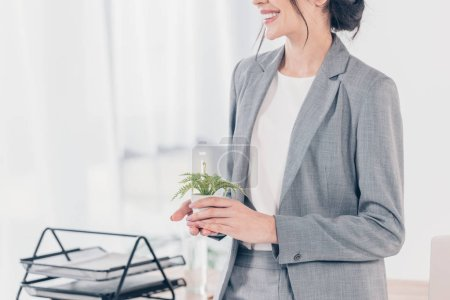 cropped view of smiling businesswoman in suit holding flowerpot in office