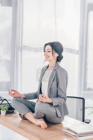 Photo pour Belle femme d'affaires souriante dans le procès méditant sur la table dans Lotus Pose dans le bureau - image libre de droit