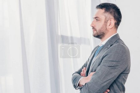Foto de Serious handsome businessman in suit with crossed arms looking at copy space - Imagen libre de derechos
