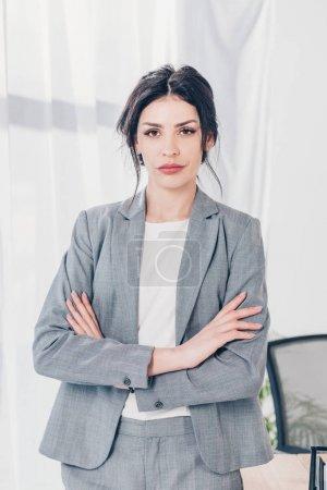 Photo pour Belle femme d'affaires confiante dans le costume avec les bras croisés regardant l'appareil-photo dans le bureau - image libre de droit