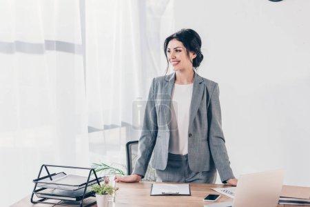 schöne lächelnde Geschäftsfrau im Anzug am Tisch im Büro mit Kopierraum