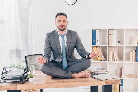 Photo pour Handsome businessman with eyes closed meditating in Lotus Pose on office desk - image libre de droit