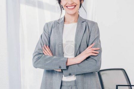 Photo pour Vue recadrée de femme d'affaires de sourire dans le procès avec les bras croisés dans le bureau - image libre de droit