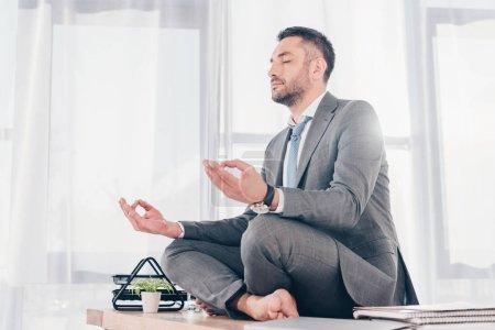 Photo pour Beau homme d'affaires avec des yeux fermés méditant dans Lotus Pose sur le bureau - image libre de droit
