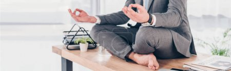 Photo pour Panoramic shot of businessman meditating in Lotus Pose on office desk - image libre de droit