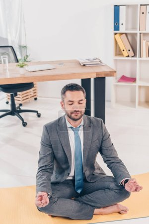 Photo pour Handsome businessman meditating in Lotus Pose on fitness mat in office - image libre de droit