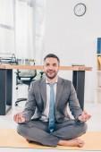 "Постер, картина, фотообои ""handsome smiling businessman meditating in Lotus Pose on fitness mat in office"""