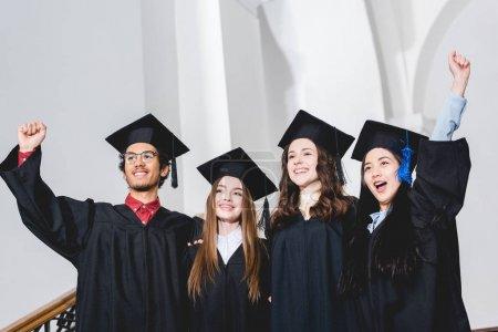 Photo pour Heureux diplômés du collège souriant et gestuel à l'université - image libre de droit