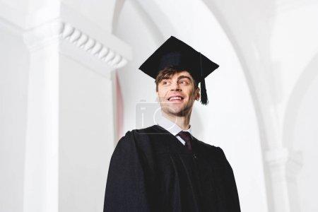 Photo pour Vue à angle bas du jeune homme heureux dans le chapeau de graduation souriant à l'université - image libre de droit