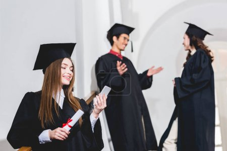 Photo pour Selective focus of attractive girl looking at smartphone while holding diploma near students - image libre de droit