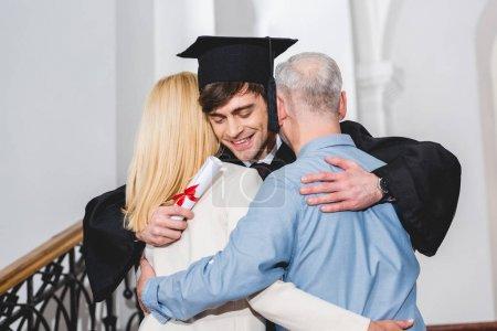 Photo pour Fils gai dans le chapeau de graduation détenant le diplôme tout en embrassant les parents - image libre de droit