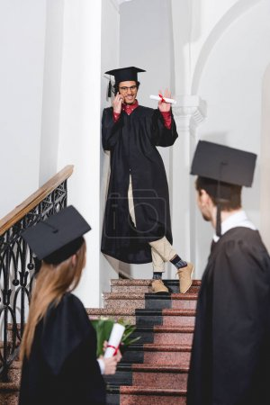 Photo pour Cheerful man talking on smartphone and waving hand to students in graduation caps - image libre de droit