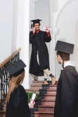 cheerful man talking on smartphone and waving hand to students in graduation caps