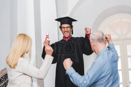 Photo pour Back view of parents gesturing near happy son in graduation cap holding diploma - image libre de droit