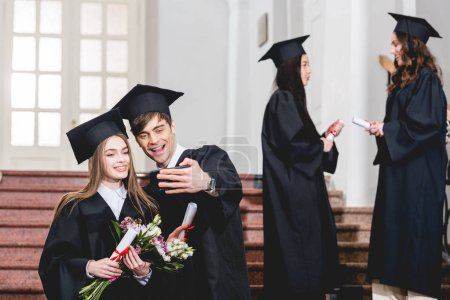 Photo pour Selective focus of handsome man and girl with flowers taking selfie near students in graduation gowns - image libre de droit