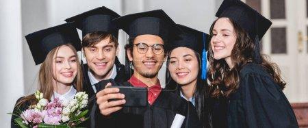 Foto de Panoramic shot of cheerful group of students in graduation caps talking selfie on smartphone - Imagen libre de derechos
