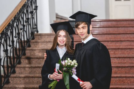 Photo pour Bel homme et jolie fille avec des fleurs souriant tout en tenant des diplômes - image libre de droit