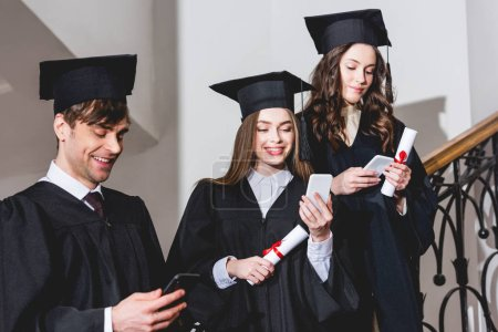 Photo pour Cheerful students in graduation gowns using smartphones while holding diplomas - image libre de droit