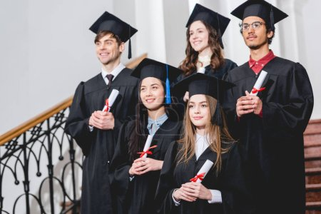 Photo for Cheerful students in graduation gowns holding diplomas in university - Royalty Free Image