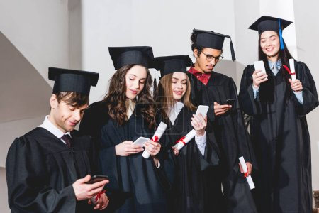 Photo pour Cheerful students in graduation caps using smartphones while holding diplomas - image libre de droit