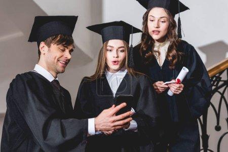 Photo pour Filles étonnées dans des chapeaux de graduation regardant le smartphone près de l'homme beau - image libre de droit