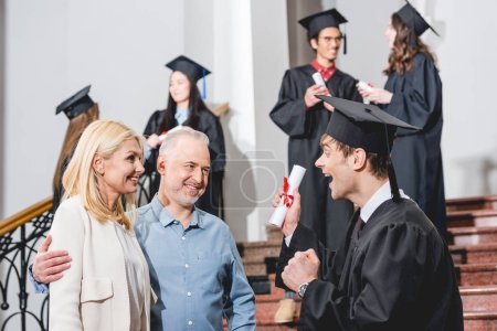Photo for Selective focus of cheerful parents looking at happy son in graduation cap gesturing while holding diploma near students - Royalty Free Image