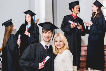 Photo pour Selective focus of mother and son in graduation cap hugging near students - image libre de droit
